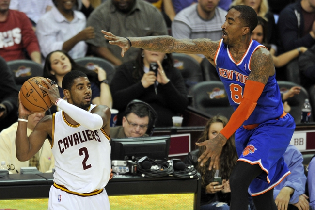 Apr 12, 2013; Cleveland, OH, USA; Cleveland Cavaliers point guard Kyrie Irving (2) looks to pass against New York Knicks shooting guard J.R. Smith (8) in the third quarter at Quicken Loans Arena. Mandatory Credit: David Richard-USA TODAY Sports