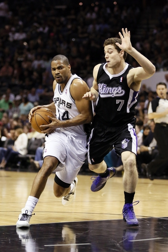 Apr 12, 2013; San Antonio, TX, USA; San Antonio Spurs guard Gary Neal (14) drives to the basket while guarded by Sacramento Kings guard Jimmer Fredette (7) during the first half at the AT&T Center. Mandatory Credit: Soobum Im-USA TODAY Sports