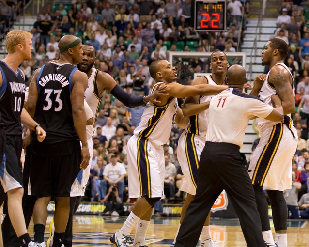 Apr 12, 2013; Salt Lake City, UT, USA; Utah Jazz players and referee Derrick Collins (11) separate Derrick Favors (far right) from Minnesota Timberwolves small forward Chase Budinger (10) and power forward Dante Cunningham (33) after Favors flagrantly fouled point guard J.J. Barea (not pictured) during the second half at EnergySolutions Arena. The Jazz won 107-100. Mandatory Credit: Russ Isabella-USA TODAY Sports