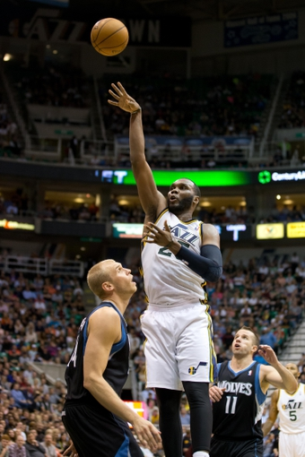 Apr 12, 2013; Salt Lake City, UT, USA; Utah Jazz center Al Jefferson (25) shoots over Minnesota Timberwolves center Greg Stiemsma (34) as point guard J.J. Barea (11) looks on during the second half at EnergySolutions Arena. The Jazz won 107-100. Mandatory Credit: Russ Isabella-USA TODAY Sports