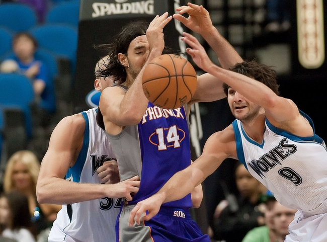 Apr 13, 2013; Minneapolis, MN, USA; Minnesota Timberwolves point guard Ricky Rubio (9) steals the ball from Phoenix Suns power forward Luis Scola (14) in the fourth quarter at the Target Center. Timberwolves won 105-93. Mandatory Credit:  Greg Smith-USA TODAY Sports