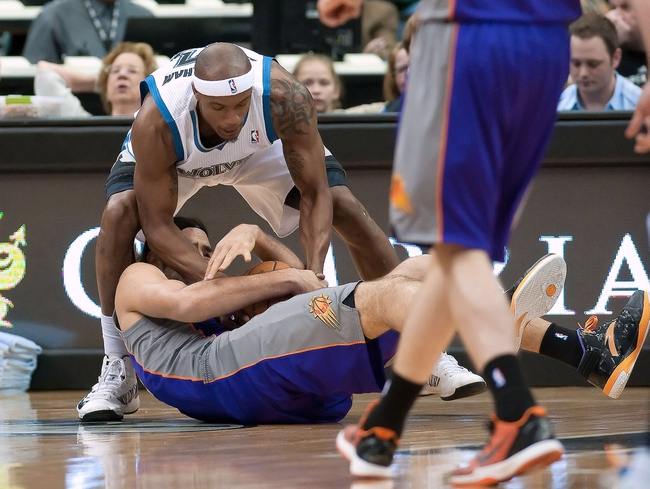 Apr 13, 2013; Minneapolis, MN, USA; Minnesota Timberwolves power forward Dante Cunningham (33) wrestles with Phoenix Suns power forward Luis Scola (14) for a loose ball during the first quarter at the Target Center. Timberwolves won 105-93. Mandatory Credit:  Greg Smith-USA TODAY Sports
