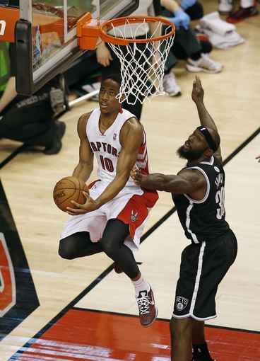 Apr 14, 2013; Toronto, ON, Canada; Toronto Raptors forward DeMar DeRozan (10) scores a basket against Brooklyn Nets forward Reggie Evans (30) at the Air Canada Centre. Mandatory Credit: Tom Szczerbowski-USA TODAY Sports