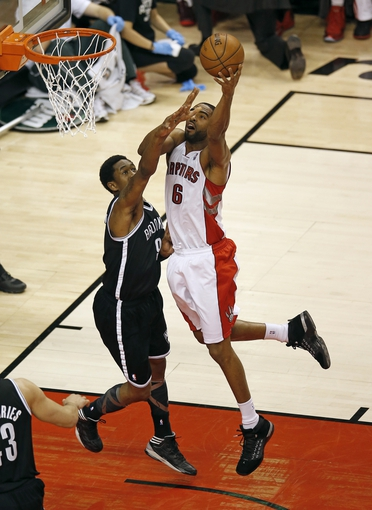 Apr 14, 2013; Toronto, ON, Canada; Toronto Raptors forward Alan Anderson (6) scores over Brooklyn Nets guard MarShon Brooks (9) at the Air Canada Centre. Mandatory Credit: Tom Szczerbowski-USA TODAY Sports