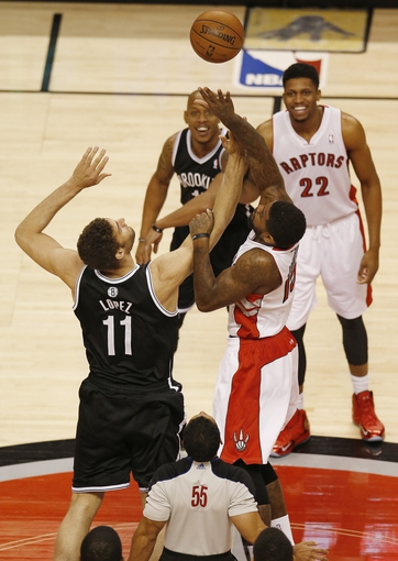 Apr 14, 2013; Toronto, ON, Canada; Toronto Raptors center Amir Johnson (15) commits a foul while tipping off against Brooklyn Nets center Brook Lopez (11) to start the game at the Air Canada Centre. Mandatory Credit: Tom Szczerbowski-USA TODAY Sports