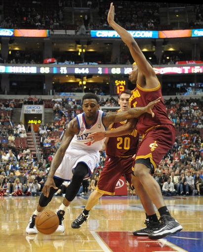 Apr 14, 2013; Philadelphia, PA, USA; Philadelphia 76ers small forward Dorell Wright (4) drives against Cleveland Cavaliers point guard Chris Quinn (20) and power forward Kevin Jones (5) during the fourth quarter at the Wells Fargo Center. The 76ers defeated the Cavaliers, 91-77. Mandatory Credit: Eric Hartline-USA TODAY Sports