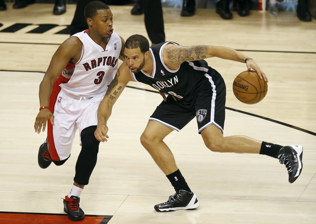 Apr 14, 2013; Toronto, ON, Canada; Brooklyn Nets point guard Deron Williams (8) makes a move to the basket against Toronto Raptors point guard Kyle Lowry (3) at the Air Canada Centre. The Raptors beat the Nets 93-87. Mandatory Credit: Tom Szczerbowski-USA TODAY Sports