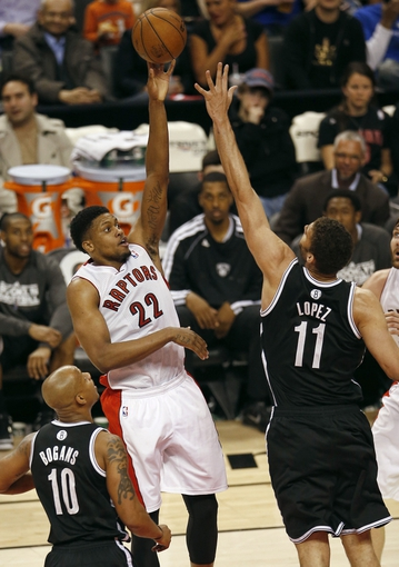 Apr 14, 2013; Toronto, ON, Canada; Toronto Raptors forward Rudy Gay (22) shoots over Brooklyn Nets center Brook Lopez (11) at the Air Canada Centre. The Raptors beat the Nets 93-87. Mandatory Credit: Tom Szczerbowski-USA TODAY Sports