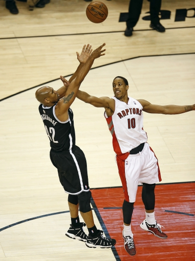 Apr 14, 2013; Toronto, ON, Canada; Brooklyn Nets forward Jerry Stackhouse (42) shoots as Toronto Raptors forward DeMar DeRozan (10) tries to block  at the Air Canada Centre. The Raptors beat the Nets 93-87. Mandatory Credit: Tom Szczerbowski-USA TODAY Sports