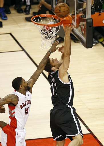 Apr 14, 2013; Toronto, ON, Canada; Brooklyn Nets center Brook Lopez (11) scores a basket against Toronto Raptors center Amir Johnson (15) at the Air Canada Centre. The Raptors beat the Nets 93-87. Mandatory Credit: Tom Szczerbowski-USA TODAY Sports