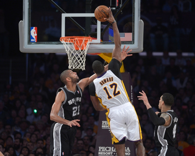 Apr 14, 2013; Los Angeles, CA, USA; Los Angeles Lakers center Dwight Howard (12) is defended by San Antonio Spurs forward Tim Duncan (21) at the Staples Center. The Lakers defeated the Spurs 91-86. Mandatory Credit: Kirby Lee-USA TODAY Sports