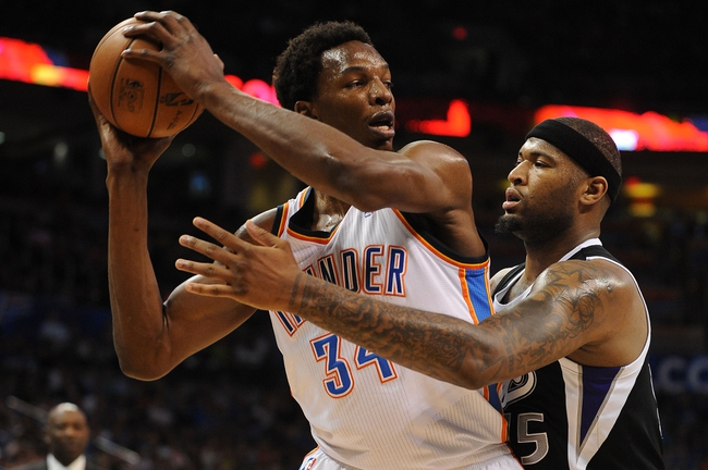 Apr 15, 2013; Oklahoma City, OK, USA; Oklahoma City Thunder center Hasheem Thabeet (34) handles the ball against Sacramento Kings center DeMarcus Cousins (15) during the first half at Chesapeake Energy Arena. Mandatory Credit: Mark D. Smith-USA TODAY Sports