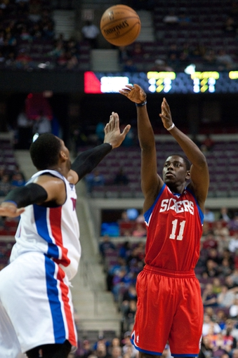 April 15, 2013; Auburn Hills, MI, USA; Philadelphia 76ers point guard Jrue Holiday (11) shoots over Detroit Pistons center Andre Drummond (1) during the first quarter at The Palace. Mandatory Credit: Tim Fuller-USA TODAY Sports