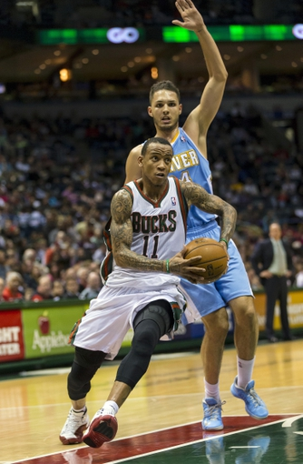 Apr 15, 2013; Milwaukee, WI, USA;  Milwaukee Bucks guard Monta Ellis (11) drives for the basket in front of Denver Nuggets guard Evan Fournier (94) during the third quarter at the BMO Harris Bradley Center.  Mandatory Credit: Jeff Hanisch-USA TODAY Sports