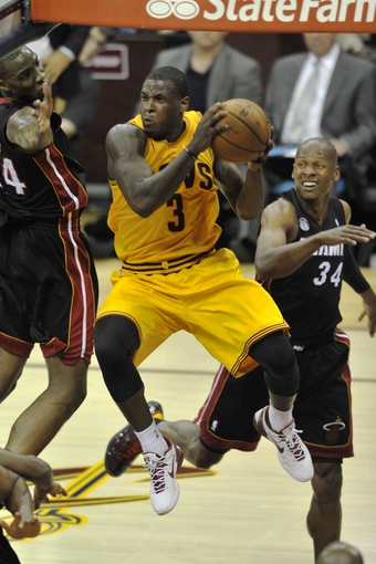Apr 15, 2013; Cleveland, OH, USA; Cleveland Cavaliers shooting guard Dion Waiters (3) drives between Miami Heat power forward Jarvis Varnado (24) and shooting guard Ray Allen (34) in the fourth quarter at Quicken Loans Arena. Mandatory Credit: David Richard-USA TODAY Sports