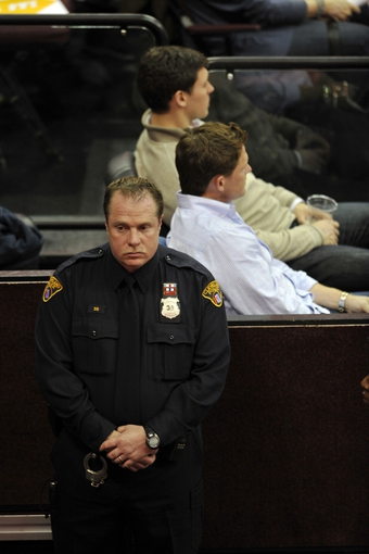 Apr 15, 2013; Cleveland, OH, USA; A Cleveland police officer stands in the aisle next to the Miami Heat bench during a game against the Cleveland Cavaliers at Quicken Loans Arena on the day of the explosions at the Boston Marathon. Mandatory Credit: David Richard-USA TODAY Sports