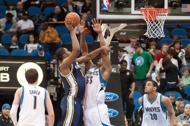 Apr 15, 2013; Minneapolis, MN, USA; Utah Jazz power forward Derrick Favors (15) shoots and Minnesota Timberwolves power forward Dante Cunningham (33) defends in the fourth quarter at Target Center. The Jazz won 96-80. Mandatory Credit:  Greg Smith-USA TODAY Sports
