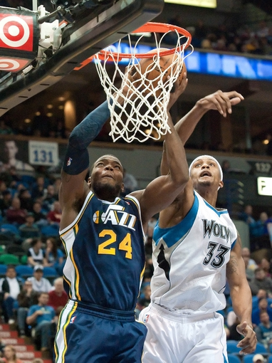 Apr 15, 2013; Minneapolis, MN, USA; Utah Jazz power forward Paul Millsap (24) shoots and Minnesota Timberwolves power forward Dante Cunningham (33) defends in the fourth quarter at Target Center. The Jazz won 96-80. Mandatory Credit:  Greg Smith-USA TODAY Sports
