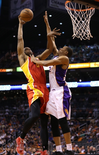 Apr. 15, 2013; Phoenix, AZ, USA: Phoenix Suns forward Wesley Johnson (right) blocks the shot of Houston Rockets forward Terrence Jones in the second quarter at the US Airways Center. Mandatory Credit: Mark J. Rebilas-USA TODAY Sports