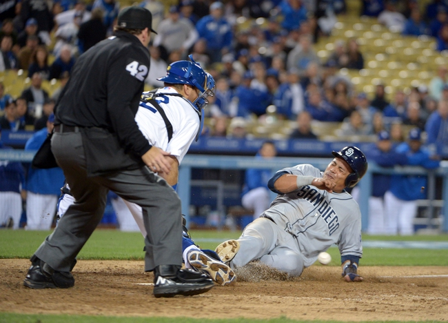 Apr 15, 2013; Los Angeles, CA, USA; San Diego Padres shortstop Everth Cabrera (right) slides into home plate to beat a throw to Los Angeles Dodgers catcher A.J. Ellis in the ninth inning at Dodger Stadium. The Padres defeated the Dodgers 6-3. Mandatory Credit: Kirby Lee-USA TODAY Sports