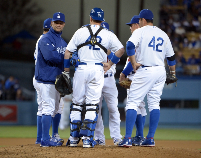 Apr 15, 2013; Los Angeles, CA, USA; Los Angeles Dodgers manager Don Mattingly (left) talks with catcher A.J. Ellis (center) and first baseman Adrian Gonzalez (right) during the game against the San Diego Padres at Dodger Stadium. The Padres defeated the Dodgers 6-3. Mandatory Credit: Kirby Lee-USA TODAY Sports