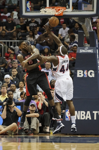 Apr 16, 2013; Atlanta, GA, USA; Atlanta Hawks power forward Ivan Johnson (44) fights for a rebound with Toronto Raptors power forward Amir Johnson (15) during the first half at Philips Arena. Mandatory Credit: Paul Abell-USA TODAY Sports