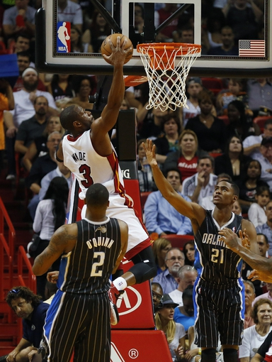 Apr 17, 2013; Miami, FL, USA;  Miami Heat shooting guard Dwyane Wade (3) makes a basket over Orlando Magic power forward Kyle O'Quinn (2) and small forward Maurice Harkless (21) in the first quarter at the American Airlines Arena.  Mandatory Credit: Robert Mayer-USA TODAY Sports