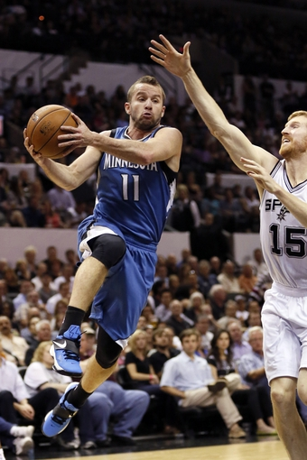 Apr 17, 2013; San Antonio, TX, USA; Minnesota Timberwolves  guard Jose Barea (11) drives to the basket as San Antonio Spurs forward Matt Bonner (15) defends during the first half at the AT&T Center. Mandatory Credit: Soobum Im-USA TODAY Sports