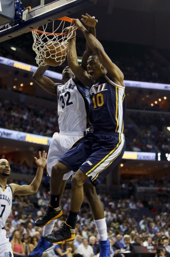 Apr 17, 2013; Memphis, TN, USA;  Utah Jazz point guard Alec Burks (10) dunks the ball against Memphis Grizzlies power forward Ed Davis (32) during the game at FedEx Forum.  Mandatory Credit: Spruce Derden   USA TODAY Sports