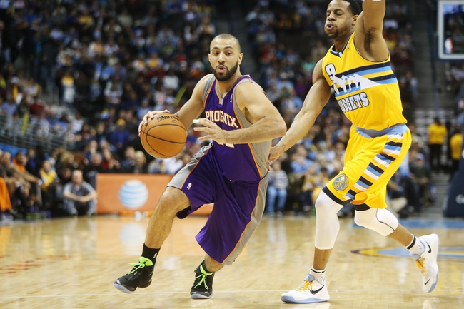 April 17, 2013; Denver, CO, USA; Phoenix Suns guard Kendall Marshall (12) drives to the basket past Denver Nuggets guard Andre Iguodala (9) during the second half at the Pepsi Center.  The Nuggets won 118-98.  Mandatory Credit: Chris Humphreys-USA TODAY Sports
