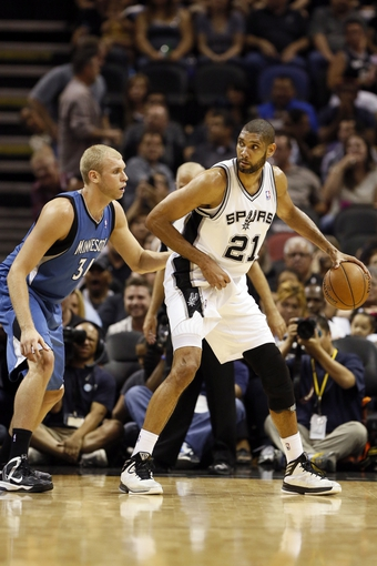Apr 17, 2013; San Antonio, TX, USA; San Antonio Spurs forward Tim Duncan (21) controls the ball as Minnesota Timberwolves center Greg Stiemsma (34) defends during the second half at the AT&T Center. The Timberwolves won 108-95.  Mandatory Credit: Soobum Im-USA TODAY Sports