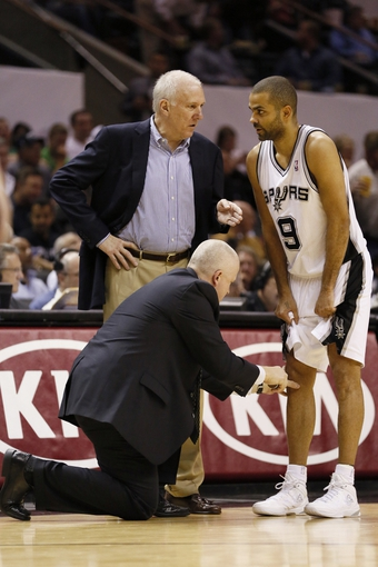Apr 17, 2013; San Antonio, TX, USA; San Antonio Spurs guard Tony Parker (9) is checked by trainer Will Sevening after he hurt his knee during the second half against the Minnesota Timberwolves at the AT&T Center. The Timberwolves won 108-95.  Mandatory Credit: Soobum Im-USA TODAY Sports