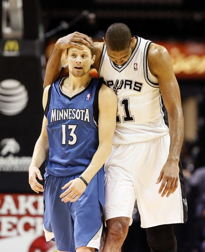 Apr 17, 2013; San Antonio, TX, USA; San Antonio Spurs forward Tim Duncan (right) hugs Minnesota Timberwolves  guard Luke Ridnour (13) after fouling him during the second half at the AT&T Center. The Timberwolves won 108-95.  Mandatory Credit: Soobum Im-USA TODAY Sports