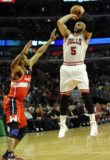 Apr 17, 2013; Chicago, IL, USA;  Chicago Bulls power forward Carlos Boozer (5) shoots over Washington Wizards power forward Trevor Booker (35) during the second half at the United Center. The Chicago Bulls defeated the Washington Wizards 95-92. Mandatory Credit: David Banks-USA TODAY Sports