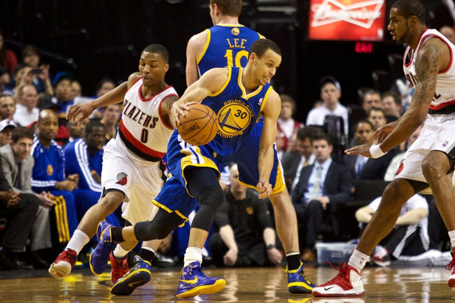 April 17, 2013; Portland, OR, USA; Golden State Warriors point guard Stephen Curry (30) dribbles around teammate power forward David Lee (10) against Portland Trail Blazers point guard Damian Lillard (0) in the first half at the Rose Garden.  Mandatory Credit: Jaime Valdez-USA TODAY Sports