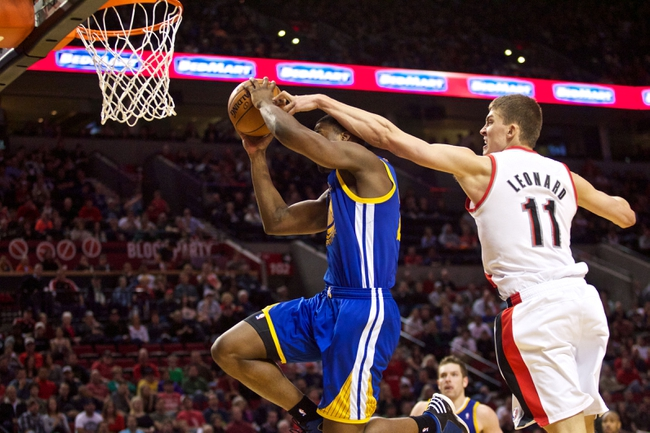 April 17, 2013; Portland, OR, USA; Portland Trail Blazers center Meyers Leonard (11) fouls Golden State Warriors small forward Harrison Barnes (40) in the second half at the Rose Garden.  Mandatory Credit: Jaime Valdez-USA TODAY Sports