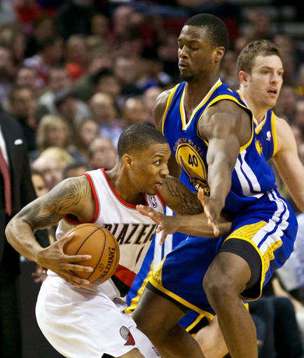 April 17, 2013; Portland, OR, USA; Portland Trail Blazers point guard Damian Lillard (0) is closely defended by Golden State Warriors small forward Harrison Barnes (40) in the second half at the Rose Garden.  Mandatory Credit: Jaime Valdez-USA TODAY Sports