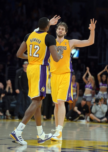 Apr 17, 2013; Los Angeles, CA, USA; Los Angeles Lakers forward Pau Gasol (16) and center Dwight Howard (12) celebrate during the fourth quarter against the Houston Rockets at the Staples Center. The Lakers defeated the Rockets 99-95 in overtime. Mandatory Credit: Kirby Lee-USA TODAY Sports