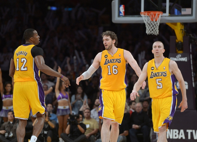 Apr 17, 2013; Los Angeles, CA, USA; Los Angeles Lakers center Dwight Howard (12), forward Pau Gasol (16) and guard Steve Blake (5) celebrate during the game against the Houston Rockets at the Staples Center. The Lakers defeated the Rockets 99-95 in overtime. Mandatory Credit: Kirby Lee-USA TODAY Sports