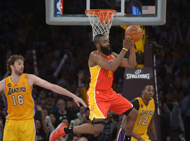 Apr 17, 2013; Los Angeles, CA, USA; Houston Rockets guard James Harden (13) passes the ball as Los Angeles Lakers forward Pau Gasol (16) and center Dwight Howard (12) defend at the Staples Center. The Lakers defeated the Rockets 99-95 in overtime. Mandatory Credit: Kirby Lee-USA TODAY Sports