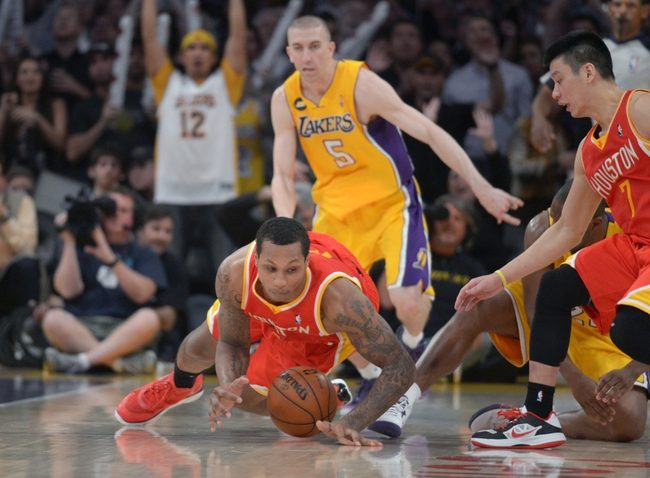 Apr 17, 2013; Los Angeles, CA, USA; Houston Rockets forward Greg Smith (4) dives for the ball as Los Angeles Lakers guard Steve Blake (5) watches at the Staples Center. The Lakers defeated the Rockets 99-95 in overtime. Mandatory Credit: Kirby Lee-USA TODAY Sports