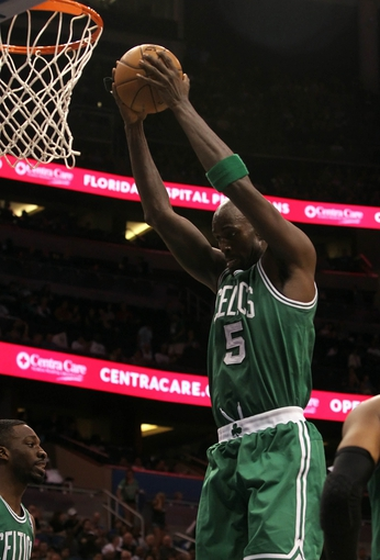 Apr 13, 2013; Orlando, FL, USA; Boston Celtics center Kevin Garnett (5) grabs a rebound against the Orlando Magic  during the second half at the Amway Center. Boston Celtics defeated the Orlando Magic 120-88. Mandatory Credit: Kim Klement-USA TODAY Sports