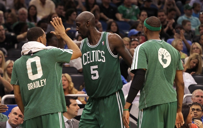 Apr 13, 2013; Orlando, FL, USA; Boston Celtics center Kevin Garnett (5) high fives small forward Paul Pierce (34) and point guard Avery Bradley (0) against the Orlando Magic during the second half at the Amway Center. Boston Celtics defeated the Orlando Magic 120-88. Mandatory Credit: Kim Klement-USA TODAY Sports