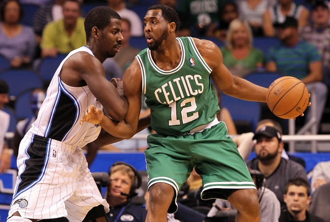 Apr 13, 2013; Orlando, FL, USA; Boston Celtics power forward D.J. White (12) drives to the basket as Orlando Magic power forward Andrew Nicholson (44) defends during the second half at the Amway Center. Boston Celtics defeated the Orlando Magic 120-88. Mandatory Credit: Kim Klement-USA TODAY Sports