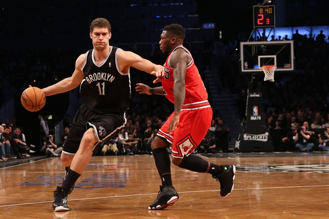 Apr 20, 2013; Brooklyn, NY, USA;  Brooklyn Nets center Brook Lopez (11) drives around Chicago Bulls point guard Nate Robinson (2) during the fourth quarter of game one of the first round of the 2013 NBA Playoffs at the Barclays Center. Brooklyn won106-89.  Mandatory Credit: Anthony Gruppuso-USA TODAY Sports