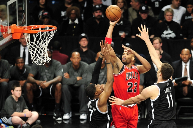 Apr 20, 2013; Brooklyn, NY, USA; Chicago Bulls power forward Taj Gibson (22) takes a shot over Brooklyn Nets shooting guard Joe Johnson (7) and center Brook Lopez (11) during the second half of game one of the first round of the 2013 NBA Playoffs at the Barclays Center. The Nets won the game 106-89. Mandatory Credit: Joe Camporeale-USA TODAY Sports