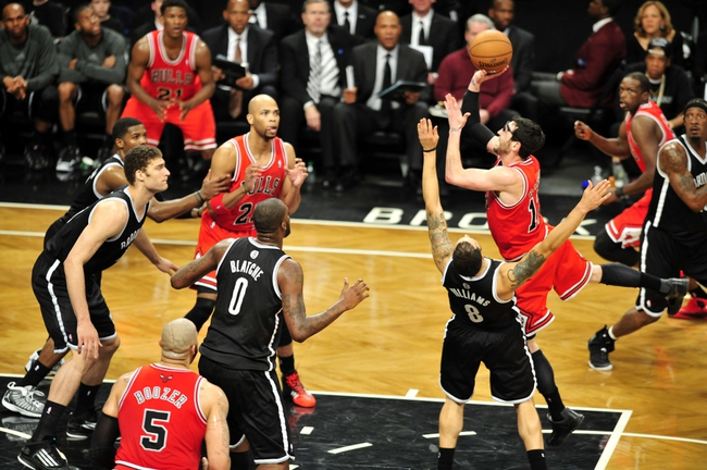 Apr 20, 2013; Brooklyn, NY, USA; Chicago Bulls shooting guard Kirk Hinrich (12) takes a shot over Brooklyn Nets point guard Deron Williams (8) during the second half of game one of the first round of the 2013 NBA Playoffs at the Barclays Center. The Nets won the game 106-89. Mandatory Credit: Joe Camporeale-USA TODAY Sports