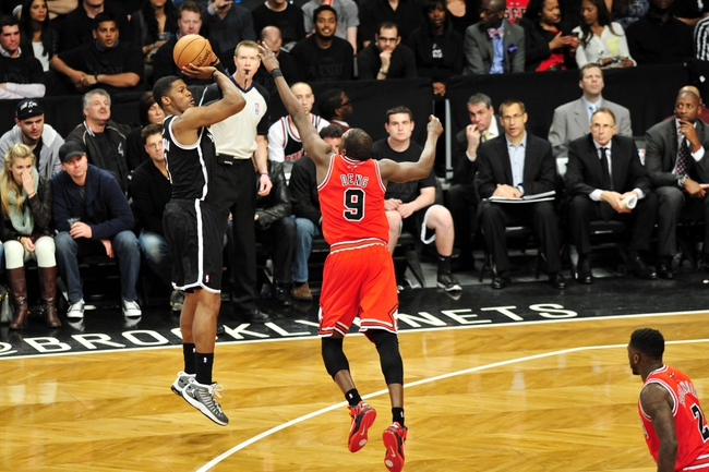 Apr 20, 2013; Brooklyn, NY, USA; Brooklyn Nets point guard C.J. Watson (1) takes a shot over Chicago Bulls small forward Luol Deng (9) during the second half of game one of the first round of the 2013 NBA Playoffs at the Barclays Center. The Nets won the game 106-89. Mandatory Credit: Joe Camporeale-USA TODAY Sports