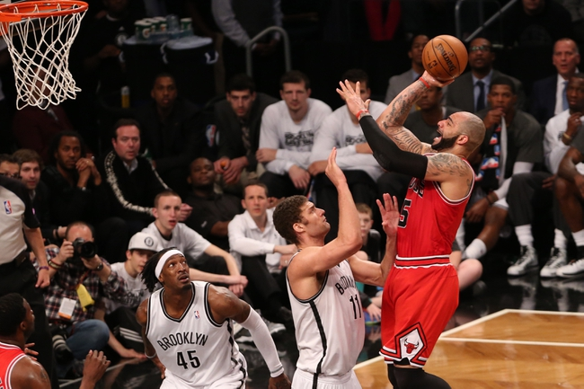 Apr 22, 2013; Brooklyn, NY, USA;  Chicago Bulls power forward Carlos Boozer (5) shoots over Brooklyn Nets center Brook Lopez (11) during the third quarter of game two in the first round of the 2013 NBA playoffs at the Barclays Center. Chicago won 90-82.  Mandatory Credit: Anthony Gruppuso-USA TODAY Sports