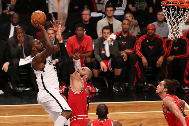Apr 22, 2013; Brooklyn, NY, USA;  Brooklyn Nets center Andray Blatche (0) shoots over Chicago Bulls power forward Carlos Boozer (5) during the fourth quarter of game two in the first round of the 2013 NBA playoffs at the Barclays Center. Chicago won 90-82.  Mandatory Credit: Anthony Gruppuso-USA TODAY Sports